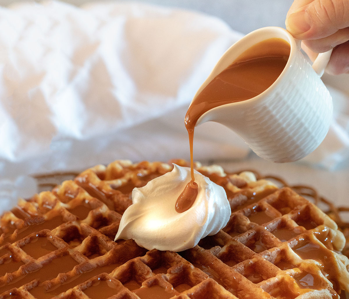 Pouring succulent caramel syrup over a stack of crispy brown waffles.