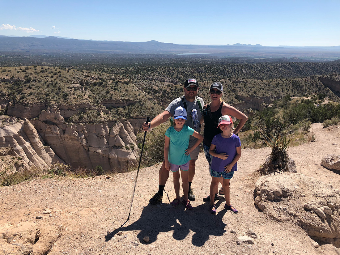 Two parents and their children stand before a rugged backdrop of desert.