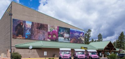 An exterior view of the Grand Canyon Imax theater with pink jeeps in the foreground.