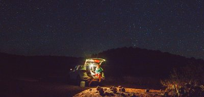 Two young women sit in the open hatchback of their vehicle in a desert campsite under a starry night sky.