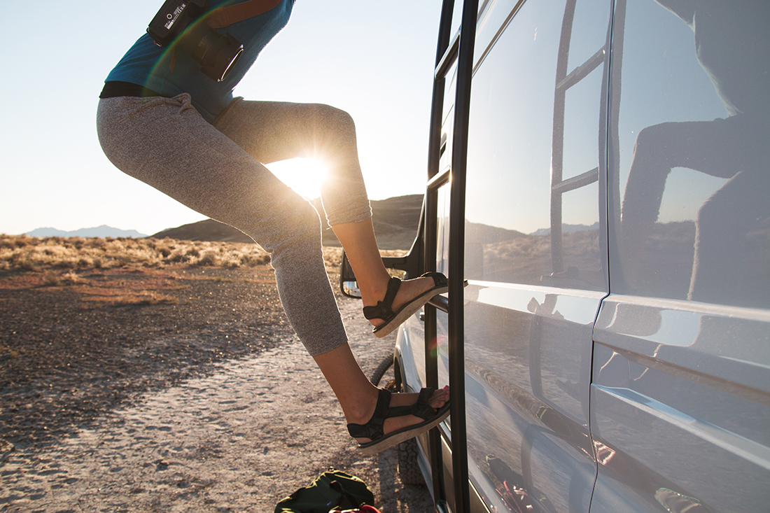 A woman climbs a ladder on the side of a white camper van as the sun rises in the distance.