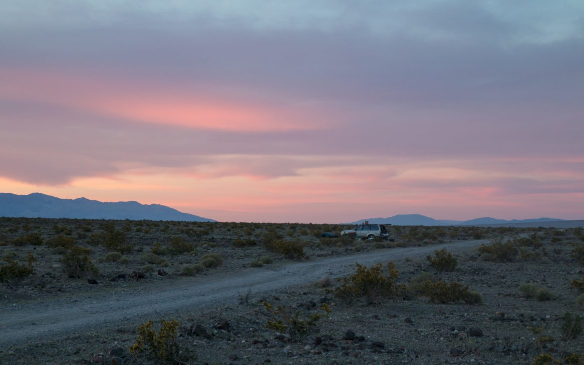 SUV parked in desert at dusk with lavender sky