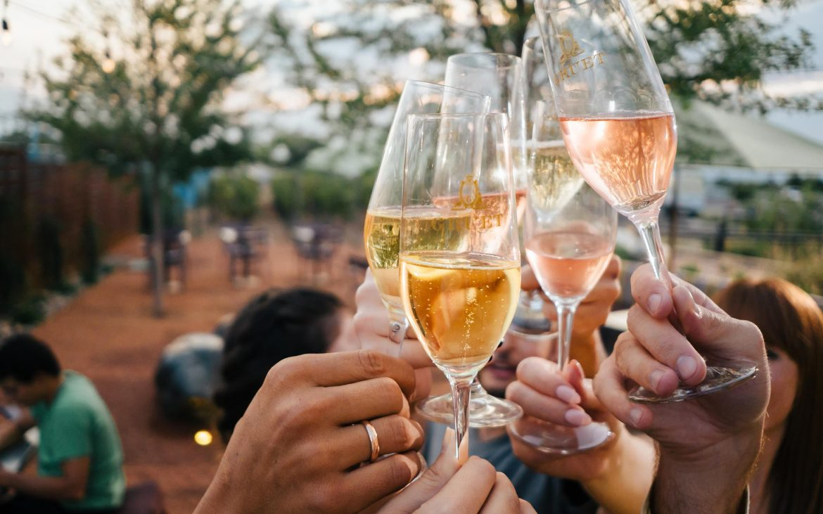 Several hands toasting champagne outside on nice day