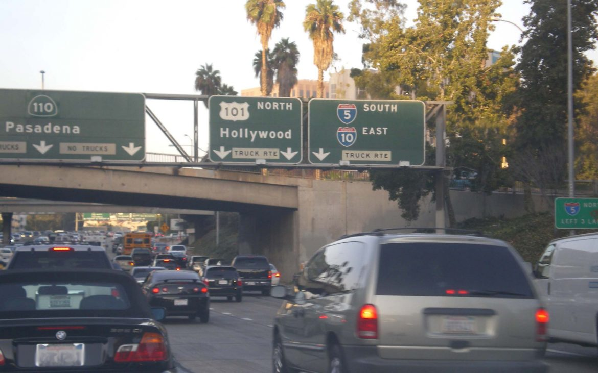 Slow traffic with brake lights shining at the junction of the Hollywood and Pasadena Freeways.