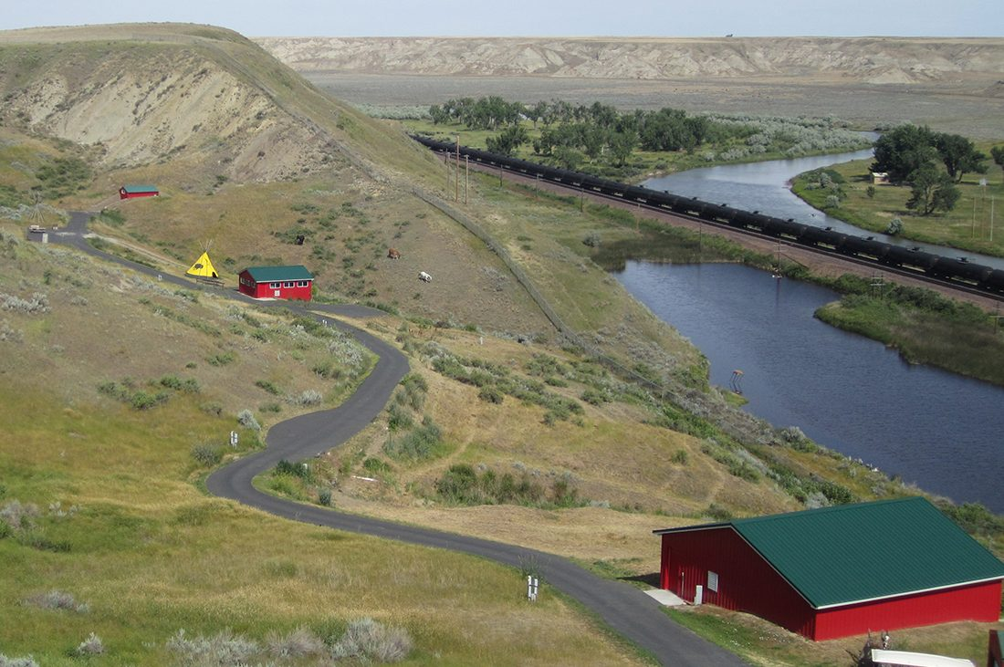A river winds through a landscape of rolling hills with a red building in the foreground.