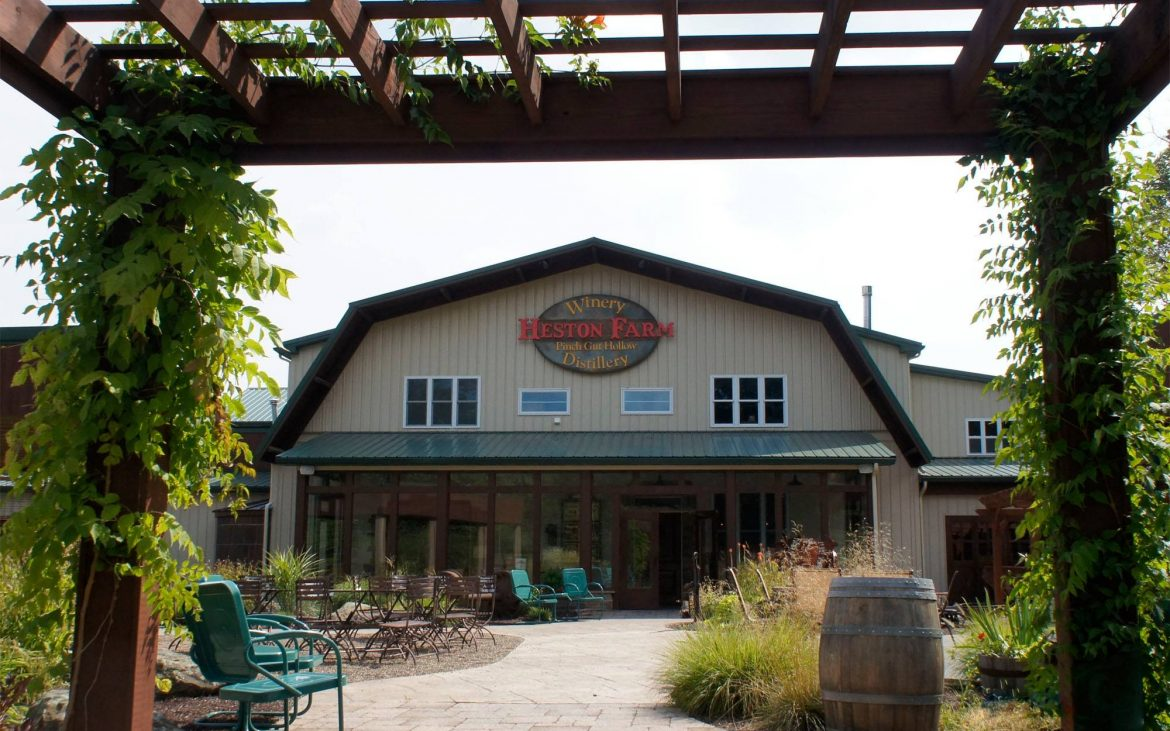 Farm building winery with outdoor lounge chairs and vines