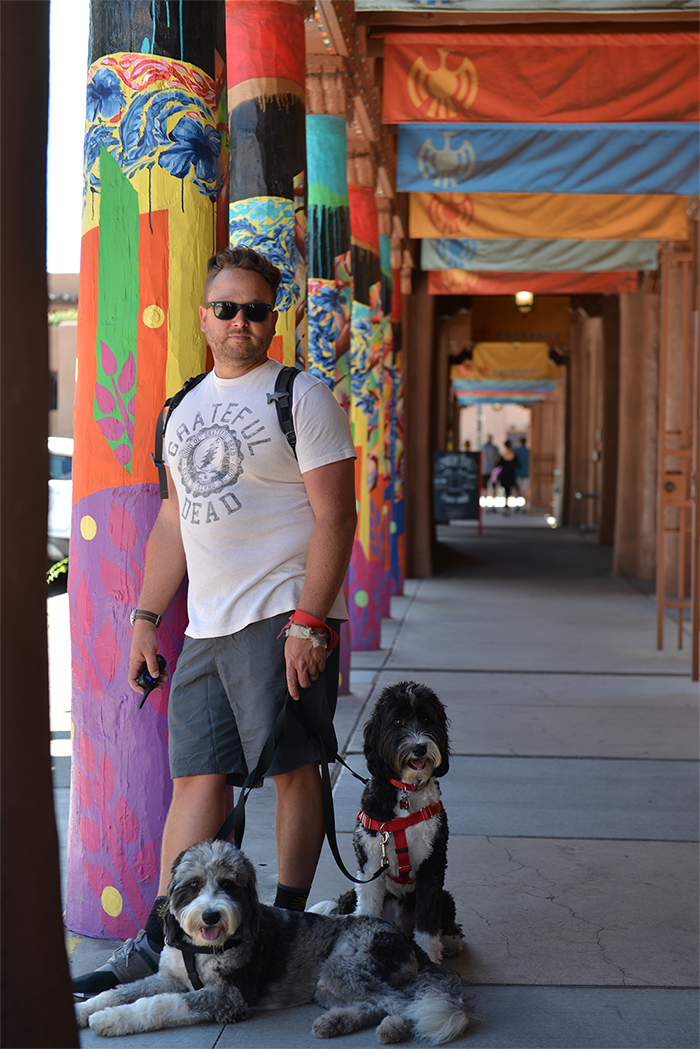 The author and his two dogs stand under an overhang at the Santa Fe Plaza.