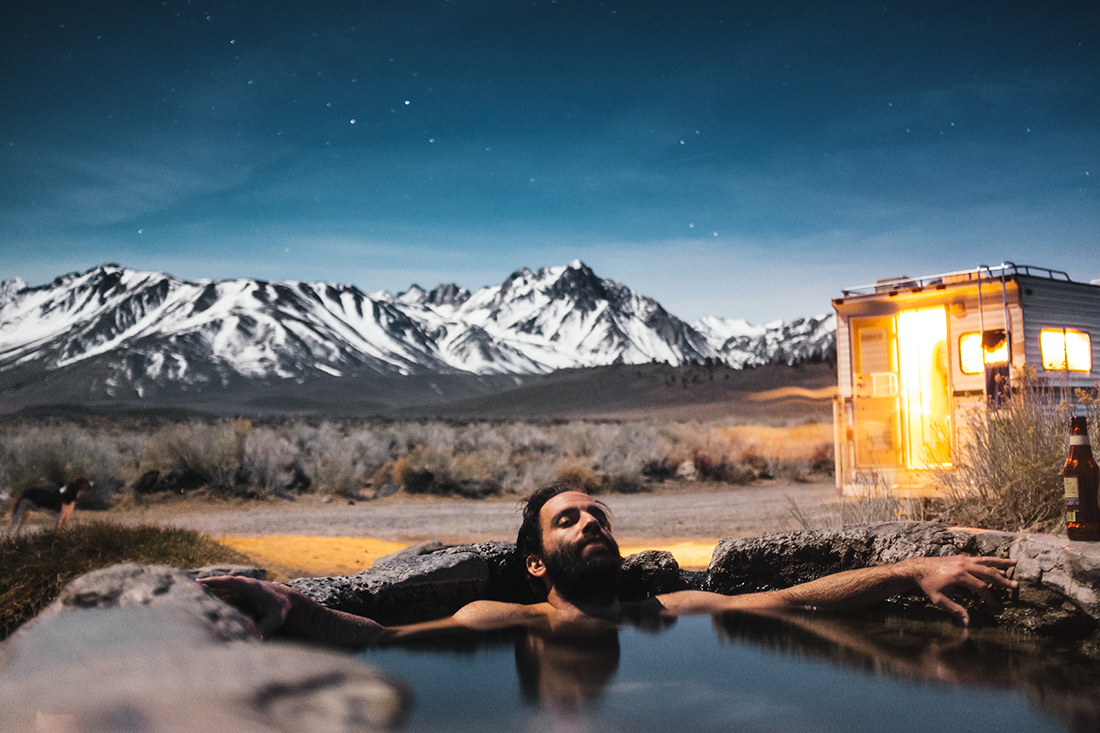 A man unwinds in a hot spring as with a truck camper and snow-covered mountains in the background.