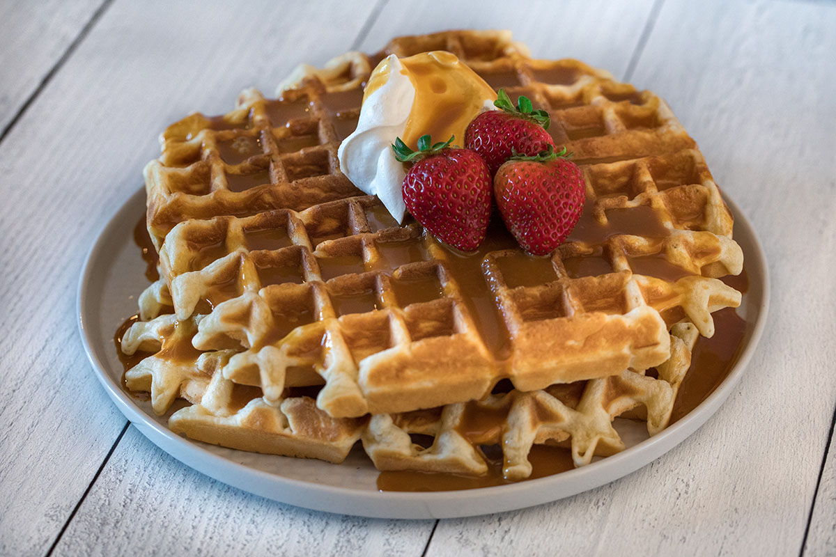 Strawberries, whipped cream and caramel syrup top a stack of waffles.