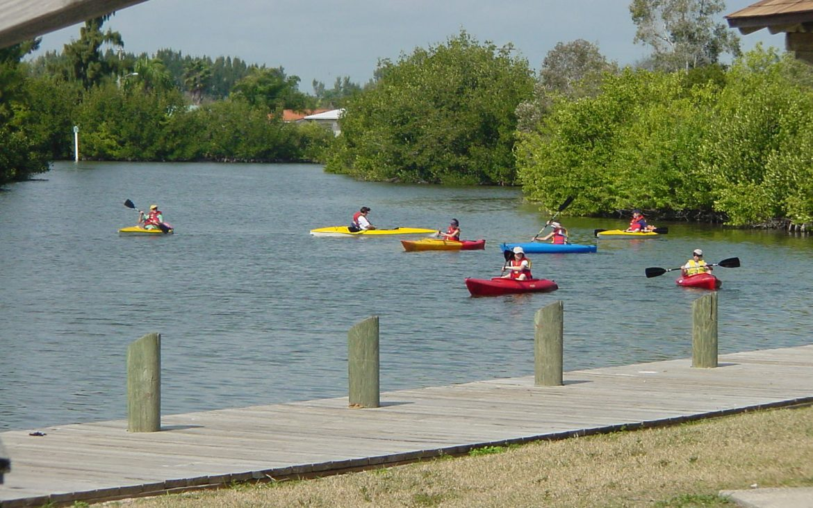 A group of kayakers navigate the bend of a river with dock in foreground.