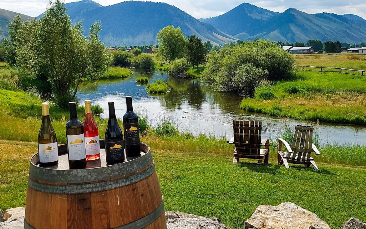 Wine barrel with five bottles outside with stream and mountains in background