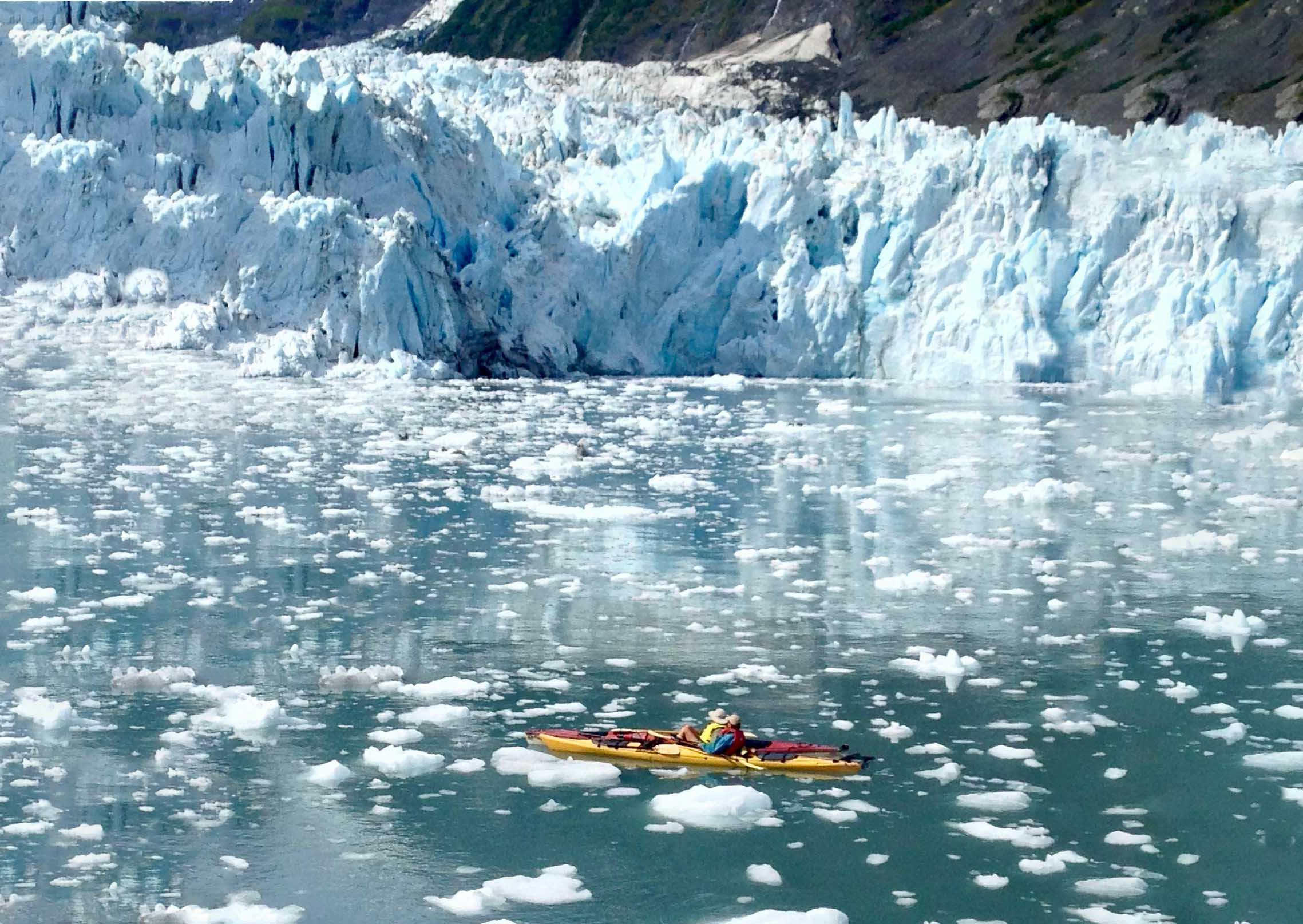 Two people kayaking at the foot of a glacier.
