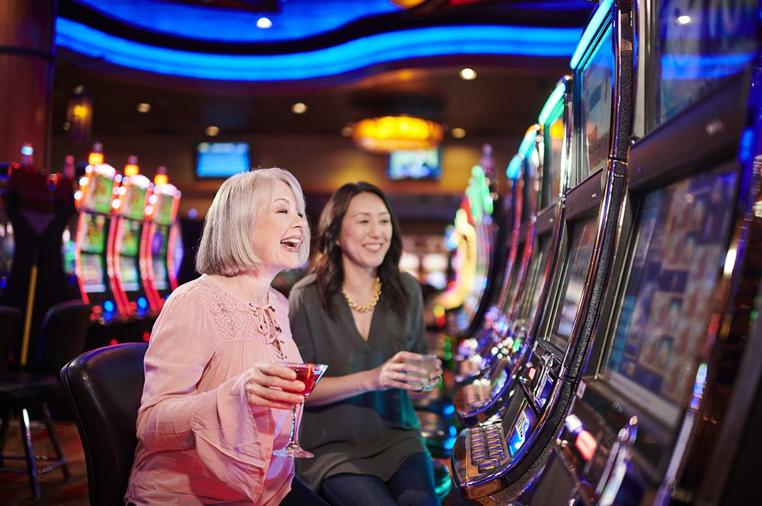 Two women sitting at a row of slot machine smile at winning score.