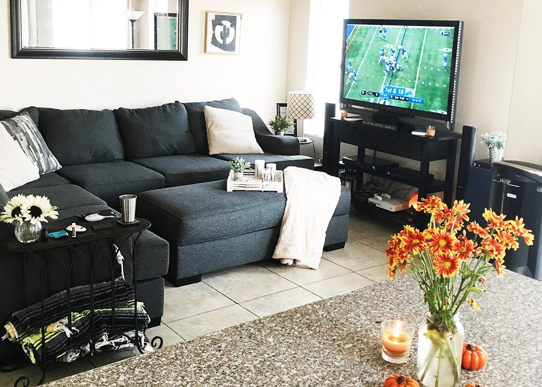 A flatscreen tv against a wall with a sofa set.