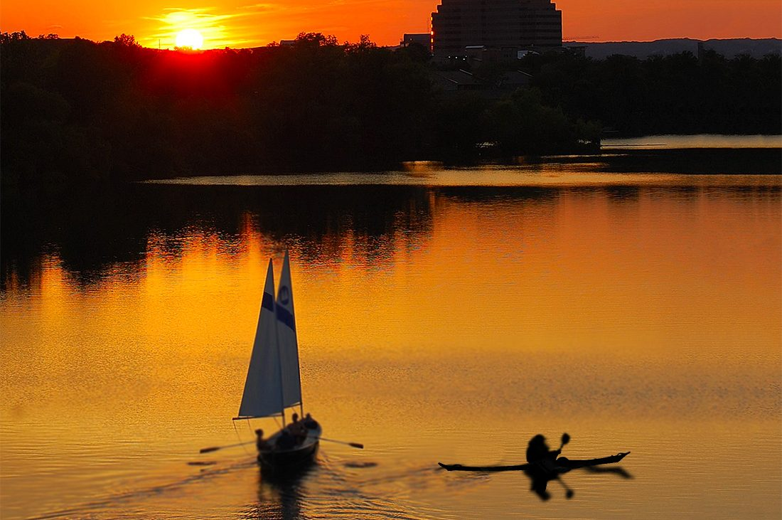 A sailboat and kayak share the golden waters of Lady Bird Lake during sunset.