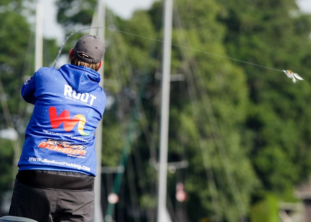 An angler in a blue windbreaker casts a line with masts of a sailboat in the background.