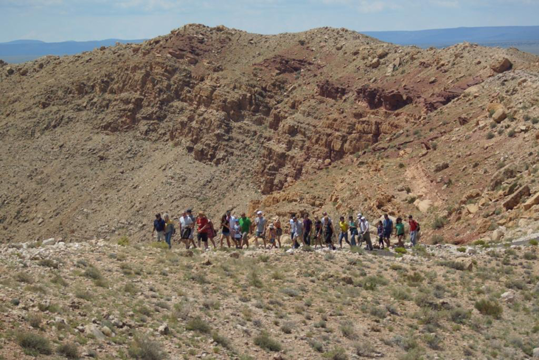 A group of about 20 people hike along the rim of Meteor Crater.