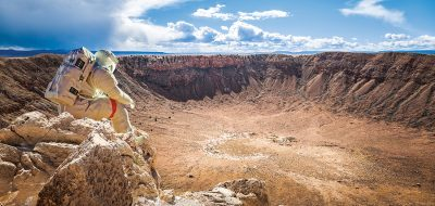 A person in a space suit looks out over Meteor Crater from the rim.