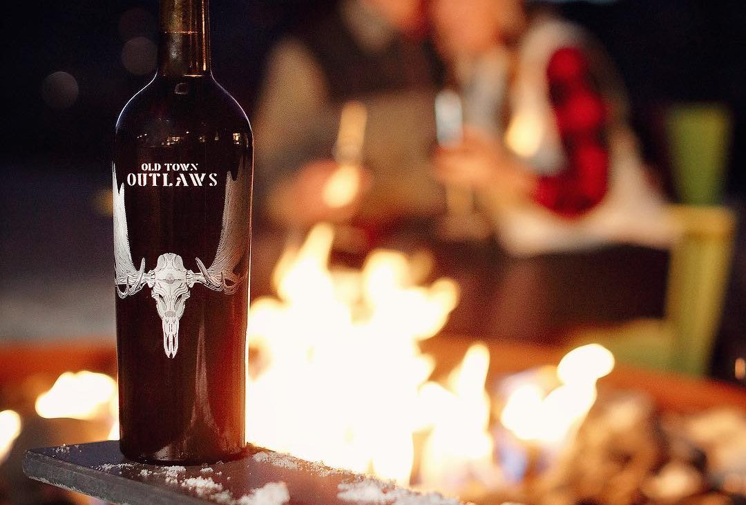 Red wine bottle in front of outdoor fire pit and people around it