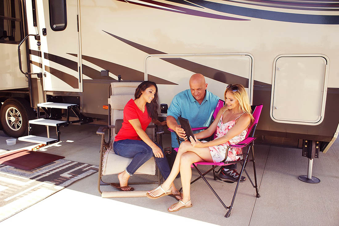 Two young woman and a muscular bald man peruse a menu outside of their motorhome.