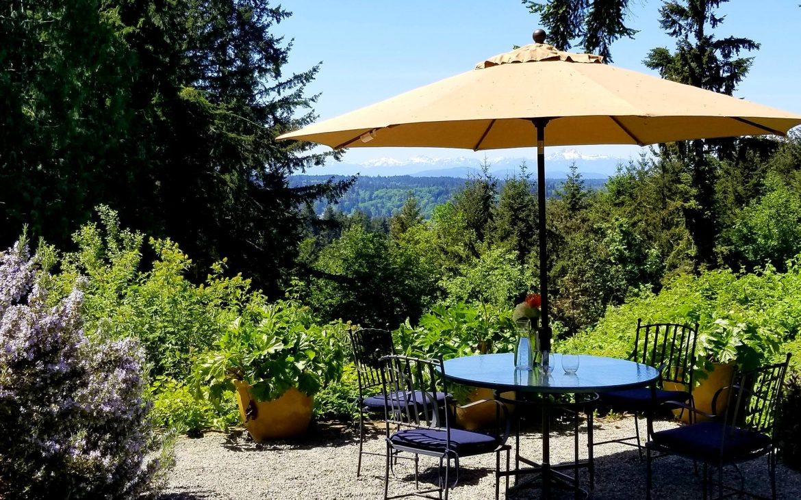 Patio table and umbrella in landscaped courtyard with beautiful view