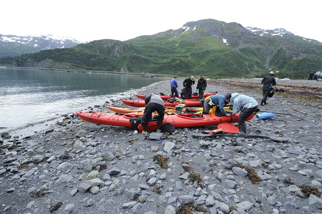Kayakers prepare their vessels on the rocky shores of Prince Williams Sound.