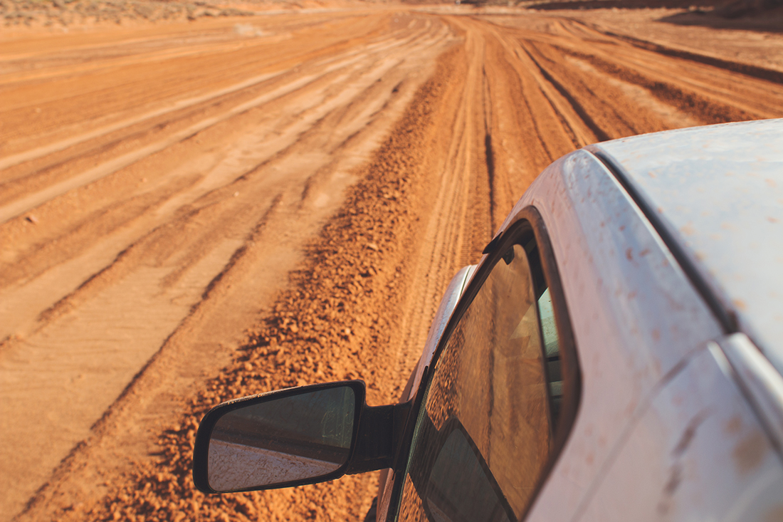 View of driver's side window from above the vehicle with tire track on a dirt road.