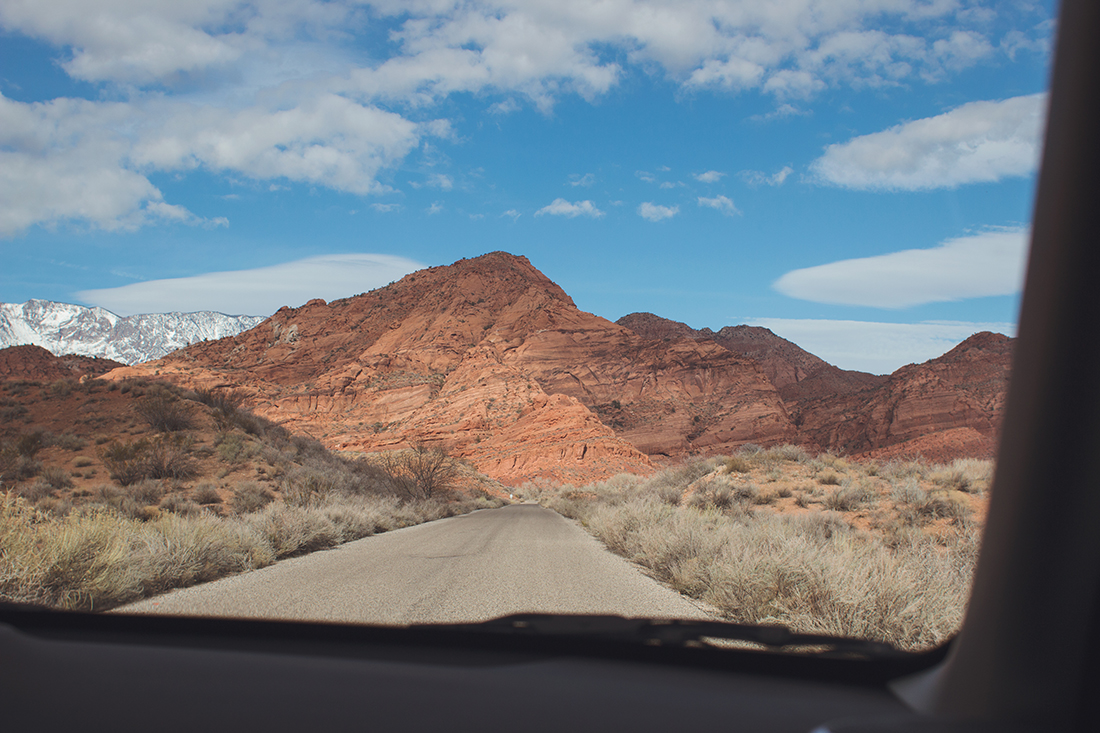 A thin, unpaved desert road leads to rugged mountains against a blue sky looming in the distance.
