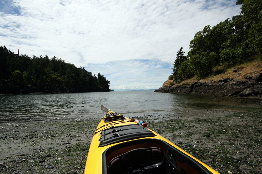 A kayak rests on the shore of an inlet surrounded by high banks and trees in the San Juan Islands.