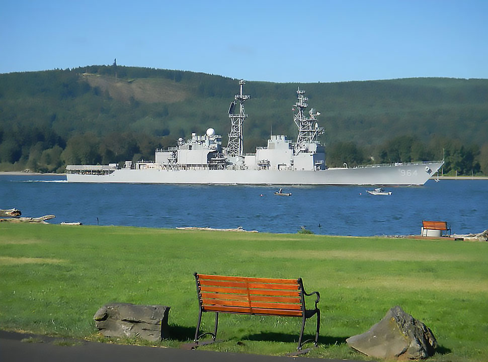 A navy vessel sails on the Columbia River with grassy bank and park bench in foreground.