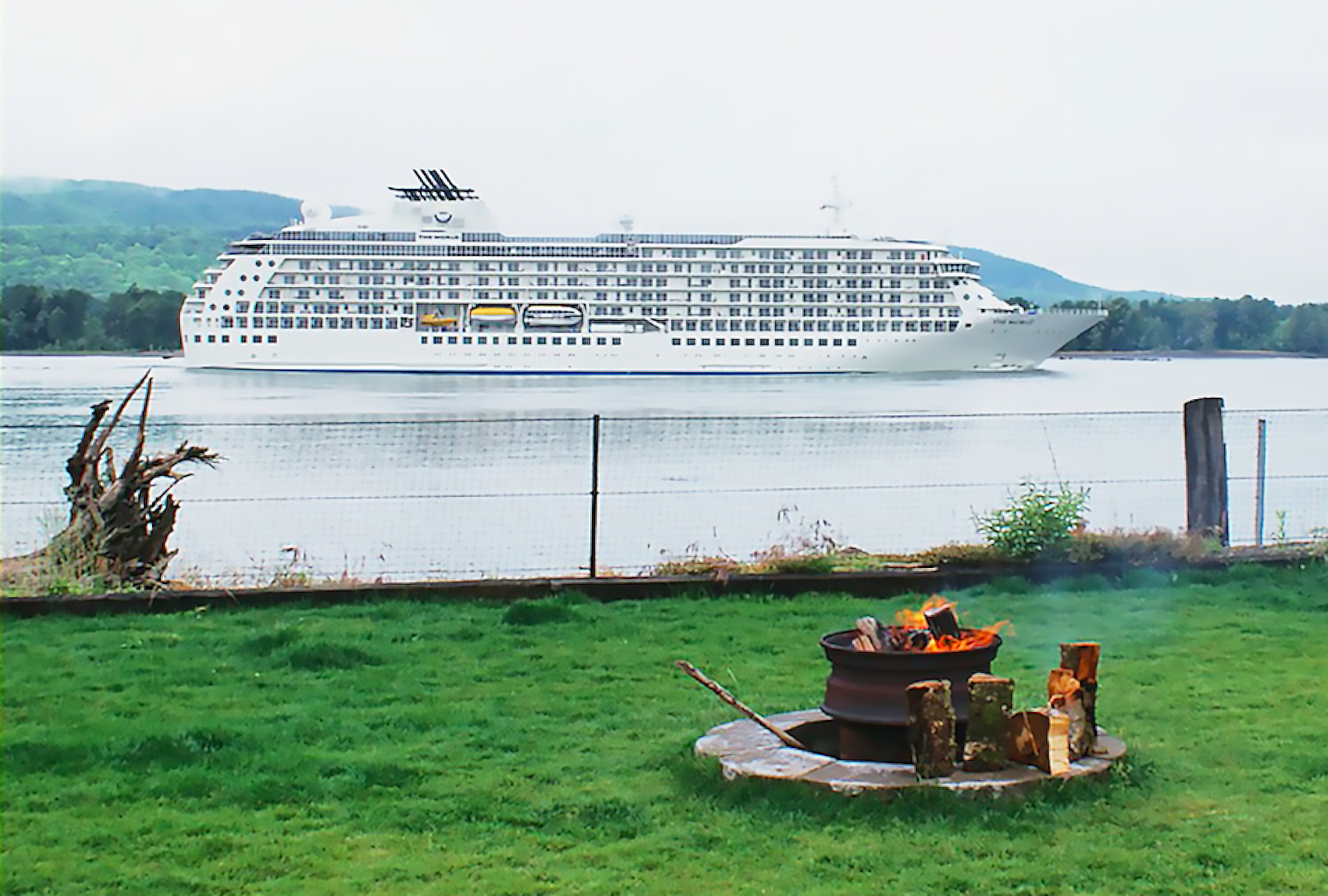 A white cruise ships sails on the Columbia River. Firepit in foreground.