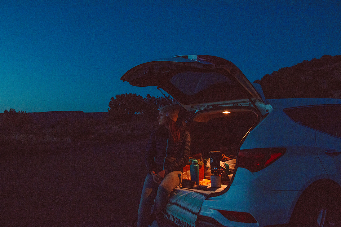 A woman gazes into the desert night as she sits in the rear of an open hatchback.