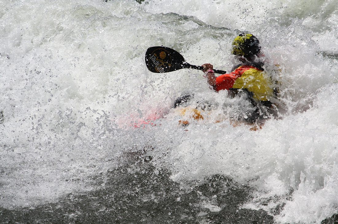 A kayaker gets overwhelmed by whitewater.