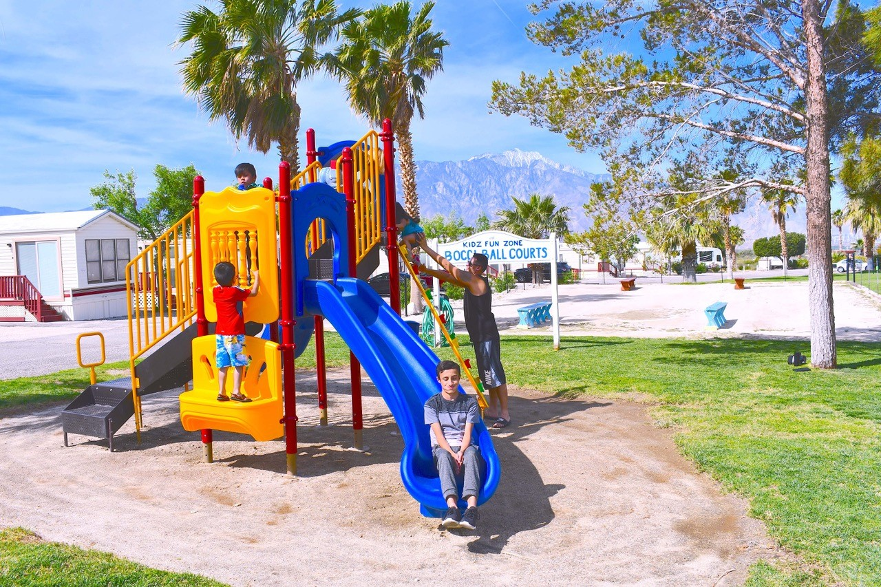 Children scamper on a colorful play structure with manufactured housing and palm trees in the background.