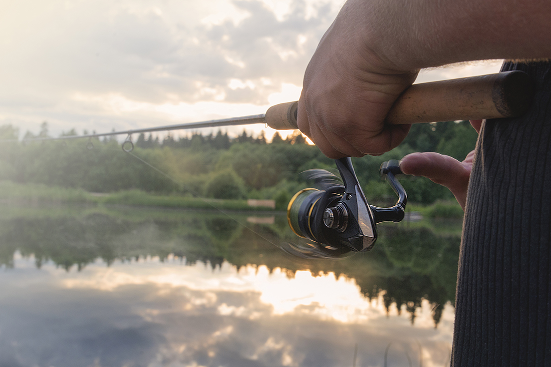 Using a spinner rod, a man slowly reels in a fish on a lake.
