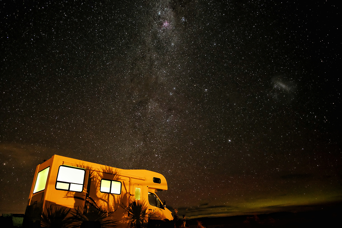 A motorhome camped under the starry night sky with interior lights shining through windows.