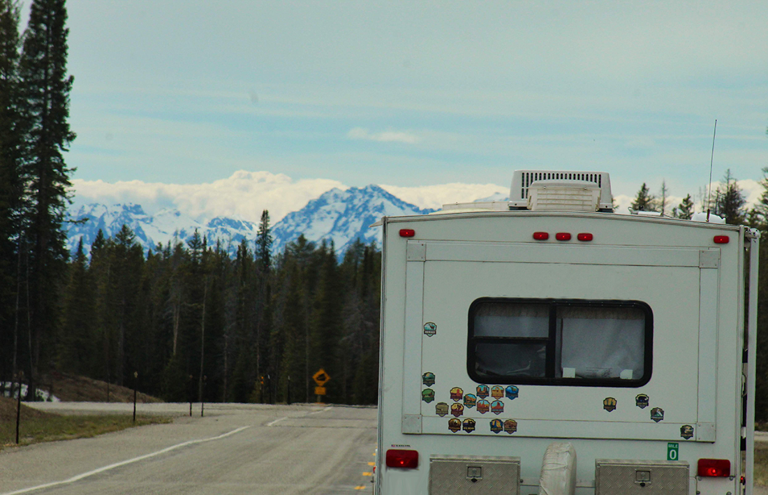 An RV driving down the highway and festooned with stickers indicated areas it has camped as trees and snow-covered peaks rise in the background.