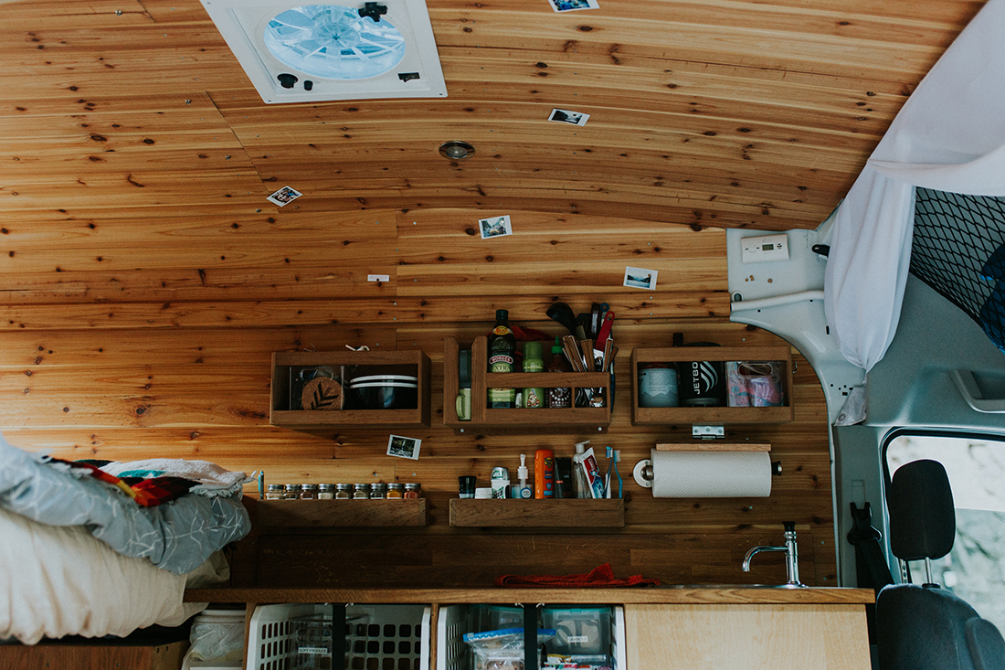 A wooden DIY camper van interior with shelves, a space rack, paper towel dispense and more.