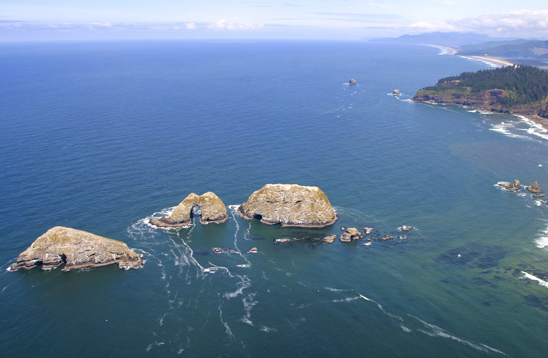 Aerial View of Three Arch Rocks National Wildlife Refuge with Cape Meares in the background.