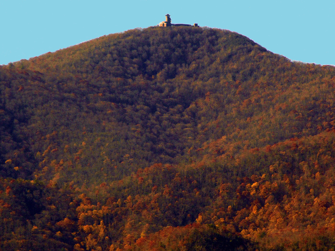 A lone watchtower sits atop a mountain covered in gold and rust foliage.