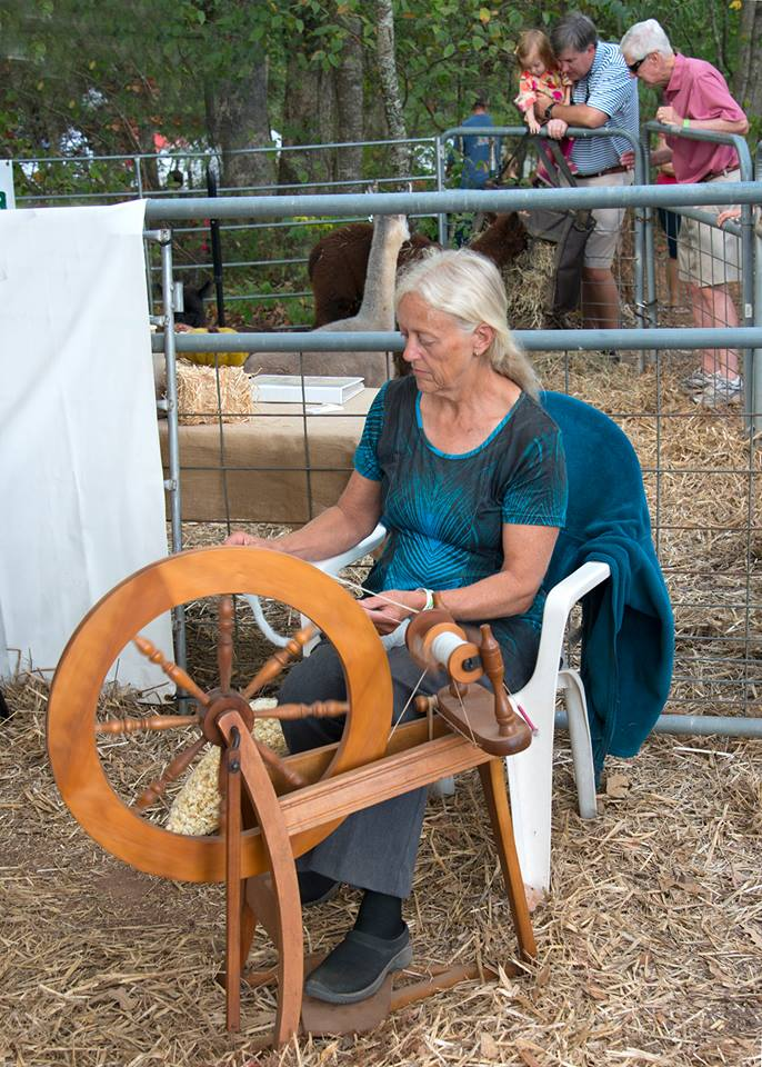 A Towns County resident demonstrates the age-old art of spinning thread on a wheel.