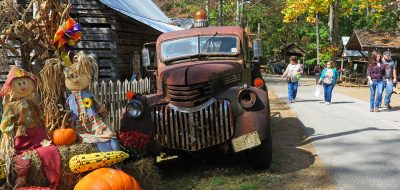 Fair attendees pass by a display of punkins surrounding an antique fire engine.