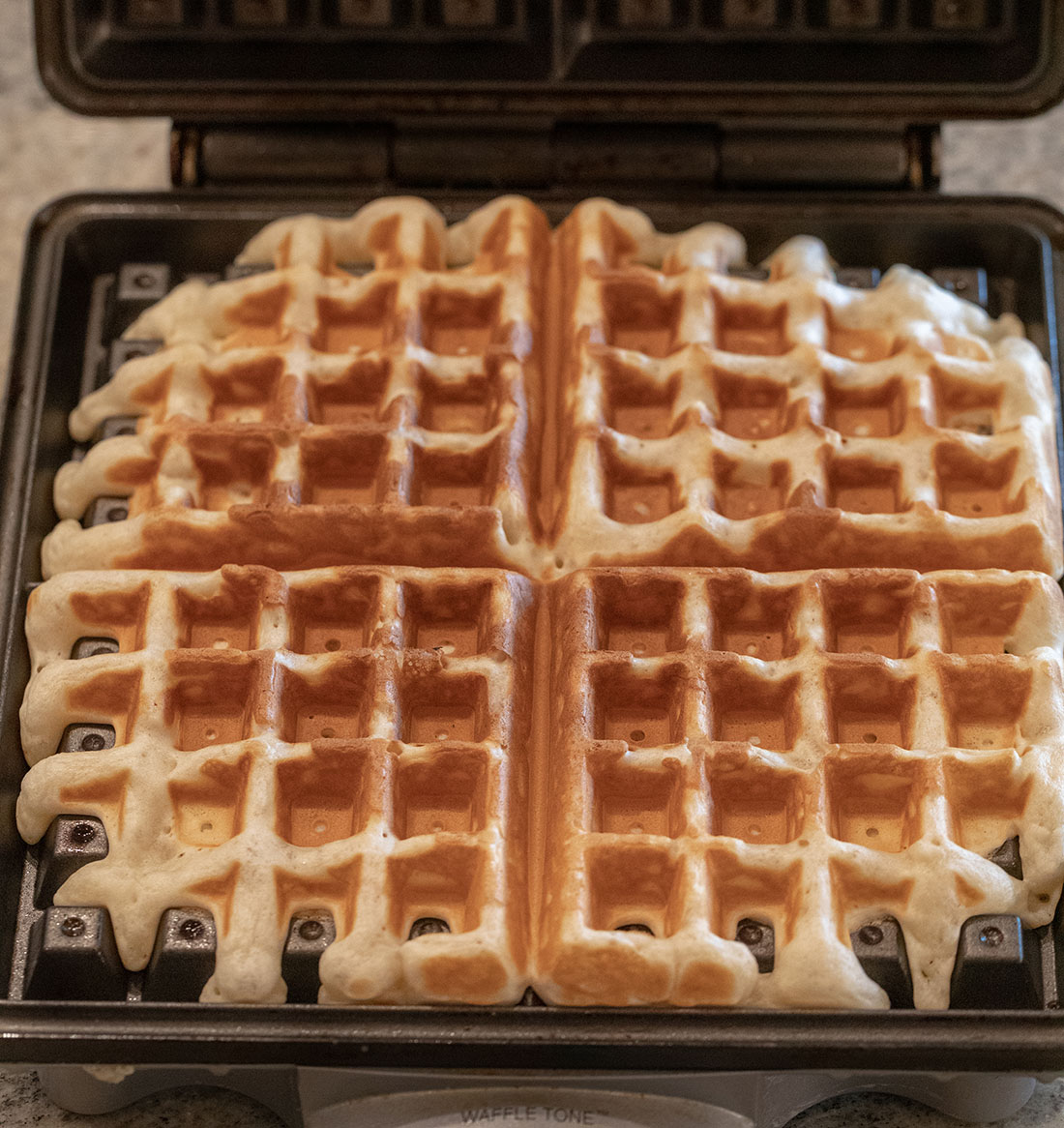 Waffles cooked golden brown in an open waffle maker.