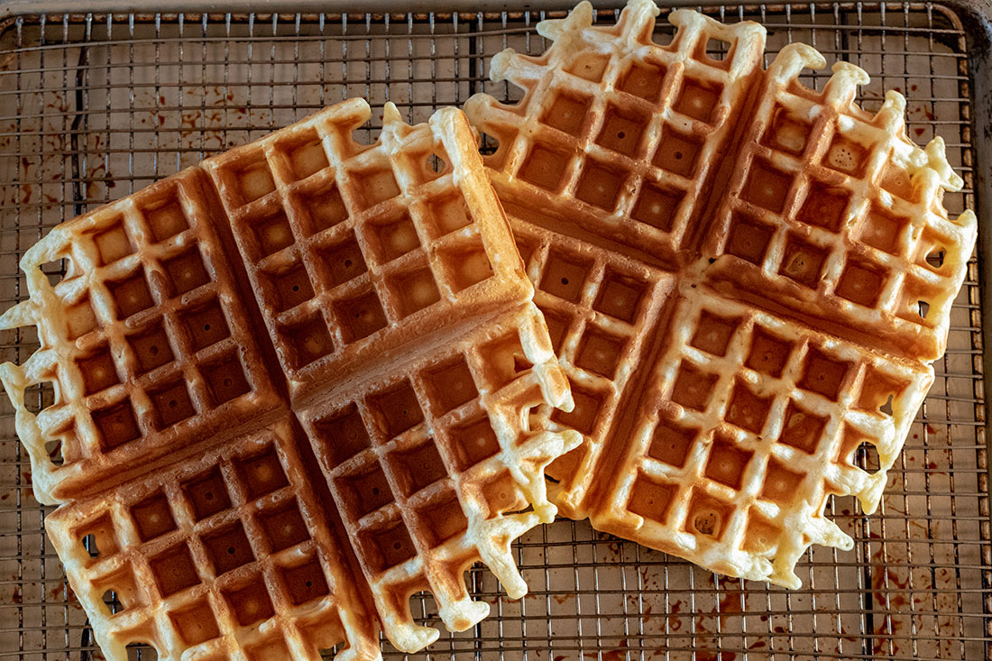 A pair of crispy brown waffles sit atop a wire rack.
