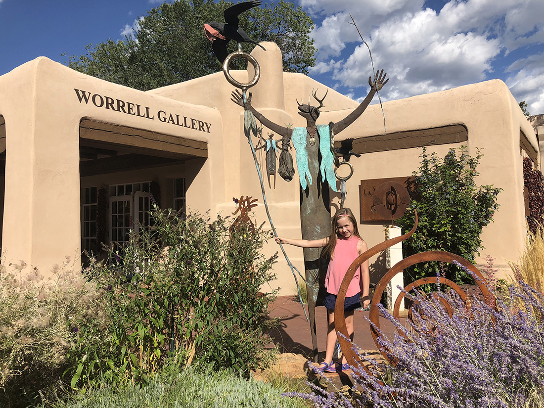 A girl stands in front of a metal sculpture of a Native American spirit at the Worrell Gallery of Santa Fe.