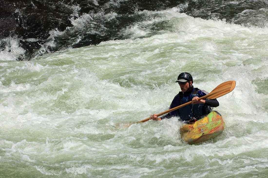 A kayaker banks against whitewater rapids in the fast-moving Youghiogheny River.