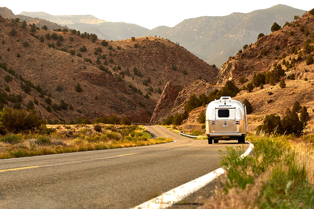 A rear view of a silver airstream that rolls down the highway between desert steep hills.