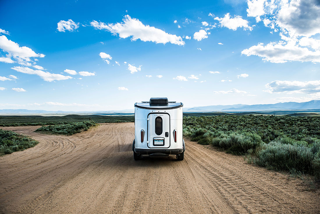 An airstream trailer driving down a dirt road.