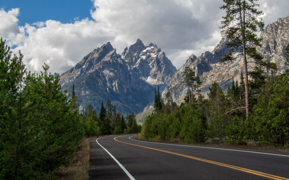 Road in Jackson Hole with snow covered mountains in background