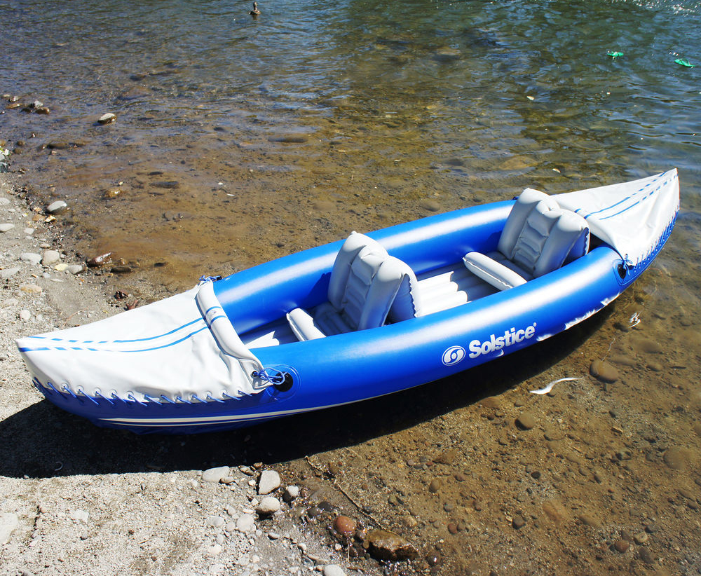 A beached blue Solstice two-seater kayak rests on the sandy shore of a clear waterway.